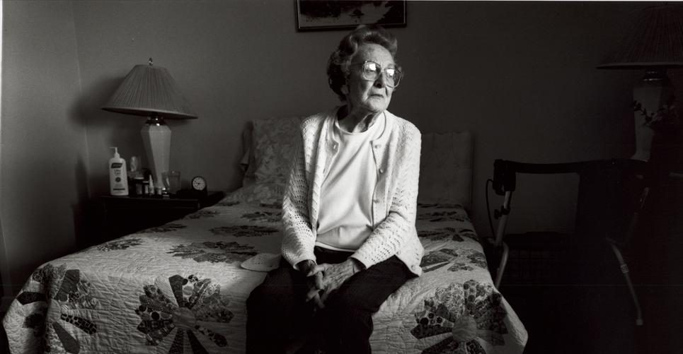 female senior sitting on end of bed